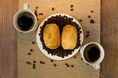 两杯咖啡用在木桌上的小圆面包 库存图片