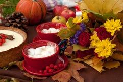 两杯咖啡用蛋白软糖,一个开胃蛋糕装饰用肉桂条和灰莓果,南瓜、苹果和a 免版税库存照片
