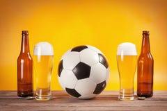 两杯啤酒和瓶临近足球 免版税库存图片