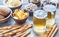 两杯啤酒用开胃菜 免版税库存图片