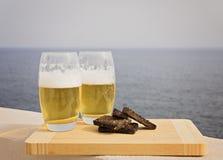 两杯啤酒用油煎方型小面包片 图库摄影