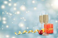 两杯在一个圣诞节礼物旁边的香槟在红色 免版税图库摄影