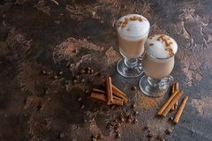 两杯在一张木土气桌上的拿铁用咖啡豆和桂香 库存照片