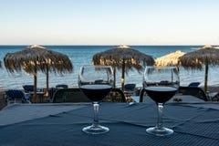 两杯在一张桌上的红酒在海滩的日落 库存照片