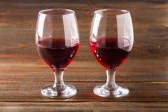 两杯在一张棕色木桌上的红葡萄酒 酒精饮料 图库摄影
