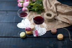 两杯在一张黑暗的桌,桃红色玫瑰花束上的红葡萄酒在包装纸的 两个白色心脏和通心面饼干 自由 图库摄影
