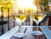 两杯在日落的酒与太阳飘动 库存图片