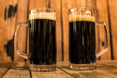 两杯在木桌上的新鲜的黑啤酒 库存图片