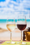 两杯在桌上的变冷的白色和红葡萄酒在海滩附近 库存图片