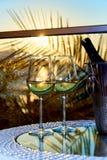两杯在玻璃桌上的白色冷的酒在日落的光芒的阳台 免版税库存图片