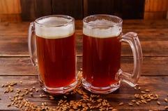两杯室内看法啤酒用在基地的麦子在一张木桌上在木背景中 免版税图库摄影