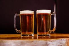两杯室内看法在一张木桌上的啤酒在黑背景中 免版税图库摄影