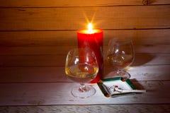 两杯科涅克白兰地、蜡烛和一根香烟在烟灰缸 库存图片