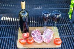 两杯红葡萄酒、牛排和蕃茄在户外烤肉 库存照片
