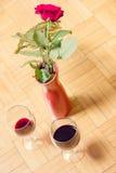 两杯红葡萄酒和红色玫瑰在花瓶 库存照片
