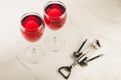 两杯红酒和拔塞螺旋在白色大理石背景/两杯红酒和木拔塞螺旋在白色大理石 免版税库存照片