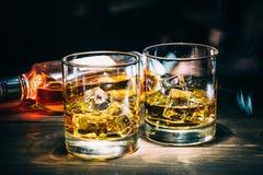 两杯苏格兰威士忌酒或科涅克白兰地与冰块和瓶酒精酒在黑暗的木背景 免版税库存照片