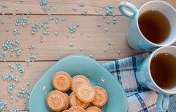 两杯茶在一块蓝色餐巾的 在一块蓝色板材的饼干在木背景 免版税库存图片