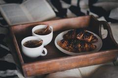 两杯茶用肉桂条和茴香星和两个新月形面包在板材 免版税库存图片