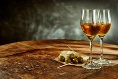 两杯酒和橄榄在木表上 免版税图库摄影