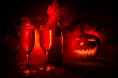 两杯酒和瓶与万圣夜-在黑暗的被定调子的有雾的背景的老起重器o灯笼 可怕万圣节的南瓜 有用 图库摄影
