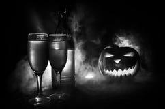 两杯酒和瓶与万圣夜-在黑暗的被定调子的有雾的背景的老起重器o灯笼 可怕万圣节的南瓜 有用 库存照片