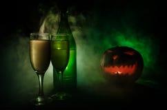 两杯酒和瓶与万圣夜-在黑暗的被定调子的有雾的背景的老起重器o灯笼 可怕万圣节的南瓜 有用 免版税库存图片