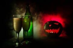 两杯酒和瓶与万圣夜-在黑暗的被定调子的有雾的背景的老起重器o灯笼 可怕万圣节的南瓜 有用 免版税图库摄影