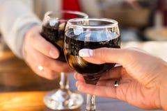 两杯酒在男人和妇女的手上有一被弄脏的背景和bokeh 库存照片
