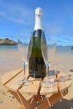 两杯香宾和瓶在天堂海岛 免版税库存图片