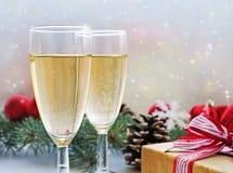 两杯香槟、礼物和圣诞装饰 免版税库存图片