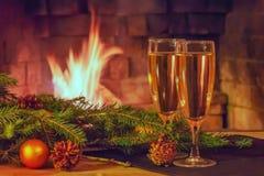 两杯香槟、装饰,圣诞树分支和一个蜡烛在一张木桌上在一个灼烧的壁炉前面 免版税库存图片