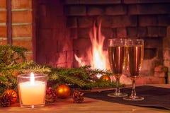 两杯香槟、装饰,圣诞树分支和一个蜡烛在一张木桌上在燃烧前面 免版税库存照片