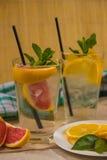 两杯玻璃水用红色桔子、柠檬、薄菏和冰 Fr 免版税库存图片