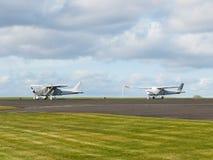 两架在机场跑道的小体育飞机逗留 免版税库存照片