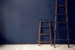 两架木梯子站立在白色地板上的蓝色墙壁 库存图片