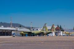 两架老军用飞机在等待的小型飞机场停放了被修理在车间外面 免版税库存图片