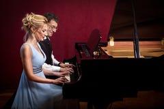 两架钢琴音乐家钢琴音乐使用,妇女和人 免版税库存照片
