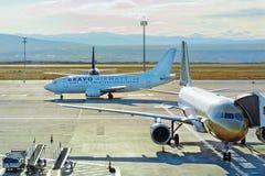 两架飞机卡塔尔和喝彩声空中航线在机场 到一jetway 免版税库存图片