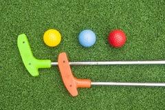 两根微型高尔夫球轻击棒和三个球 库存图片