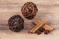 两根棕色球、八角和肉桂条在棕色木板 免版税库存照片