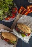 两根热狗用烤香肠、蕃茄和胡椒在木ta 库存照片