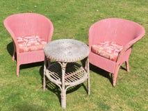 两桃红色室外椅子和表坐草 免版税库存照片