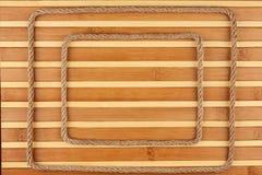 两框架由绳索,在一张竹席子的背景的谎言制成,有您的文本的地方的 免版税库存照片