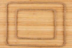 两框架由绳索,在一张竹席子的背景的谎言制成,有您的文本的地方的 免版税库存图片