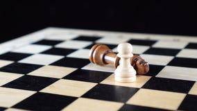 两棋典当和国王有被征服的黑棋子的说谎在它的边和白色典当的站立挺直 股票录像