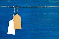 两棕色和垂悬在蓝色背景的一条绳索的白色白纸价牌或者标号组 免版税图库摄影