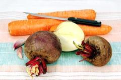 两棵未加工的甜菜、三棵红萝卜、葱和刀子。 免版税库存照片