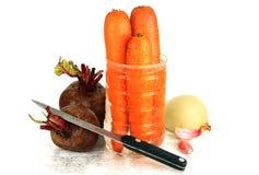 两棵未加工的甜菜、三棵红萝卜、葱和刀子。 免版税图库摄影