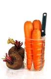 两棵未加工的甜菜、三棵红萝卜和刀子。 免版税库存图片